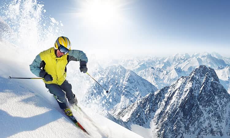 Man skiing on a moutain, sun im background and more mountains.