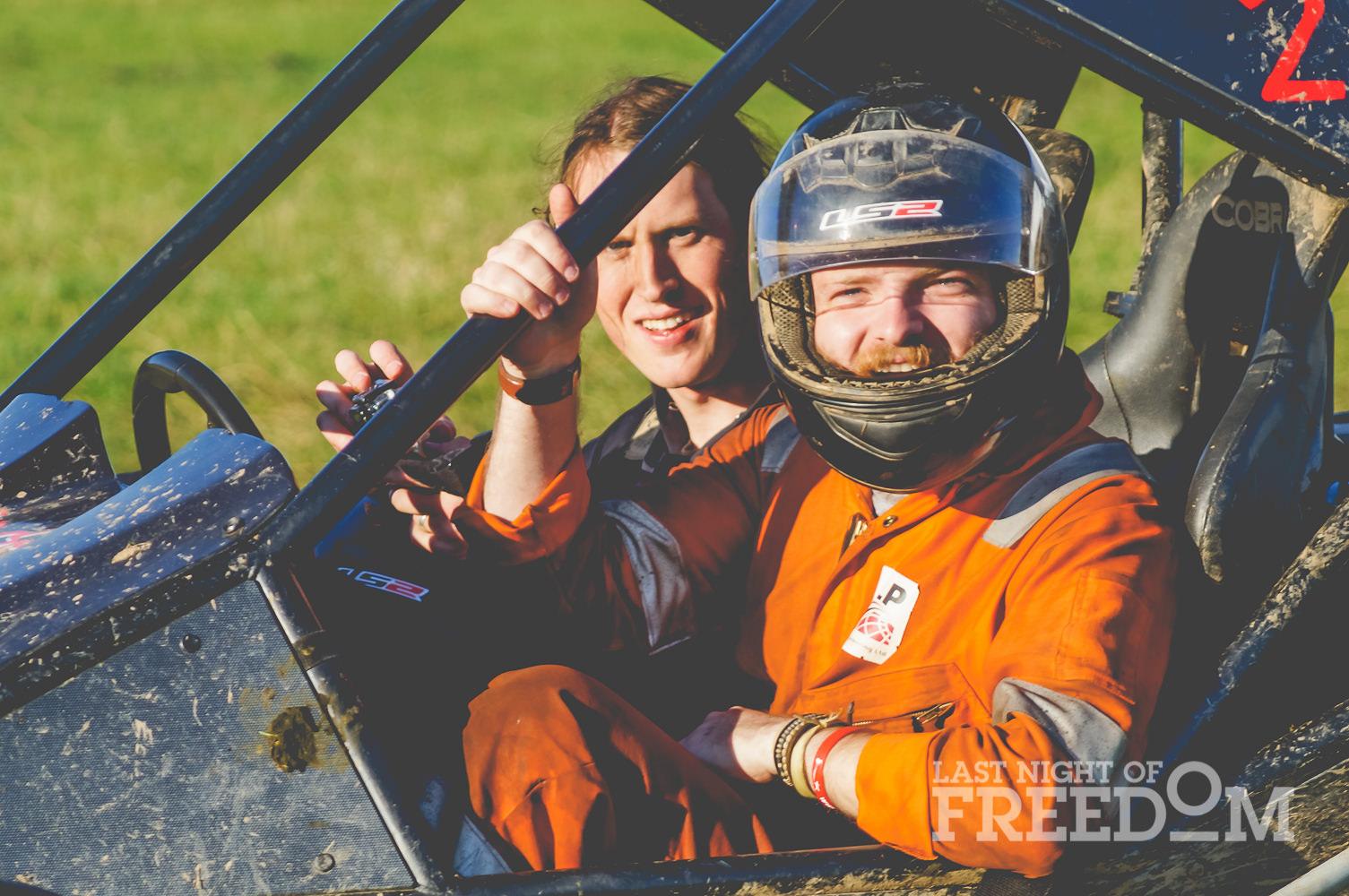 Two men in a rage buggy, one wearing a helmet