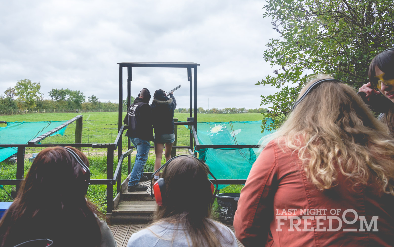 A girl firing a gun with lots of people watching her