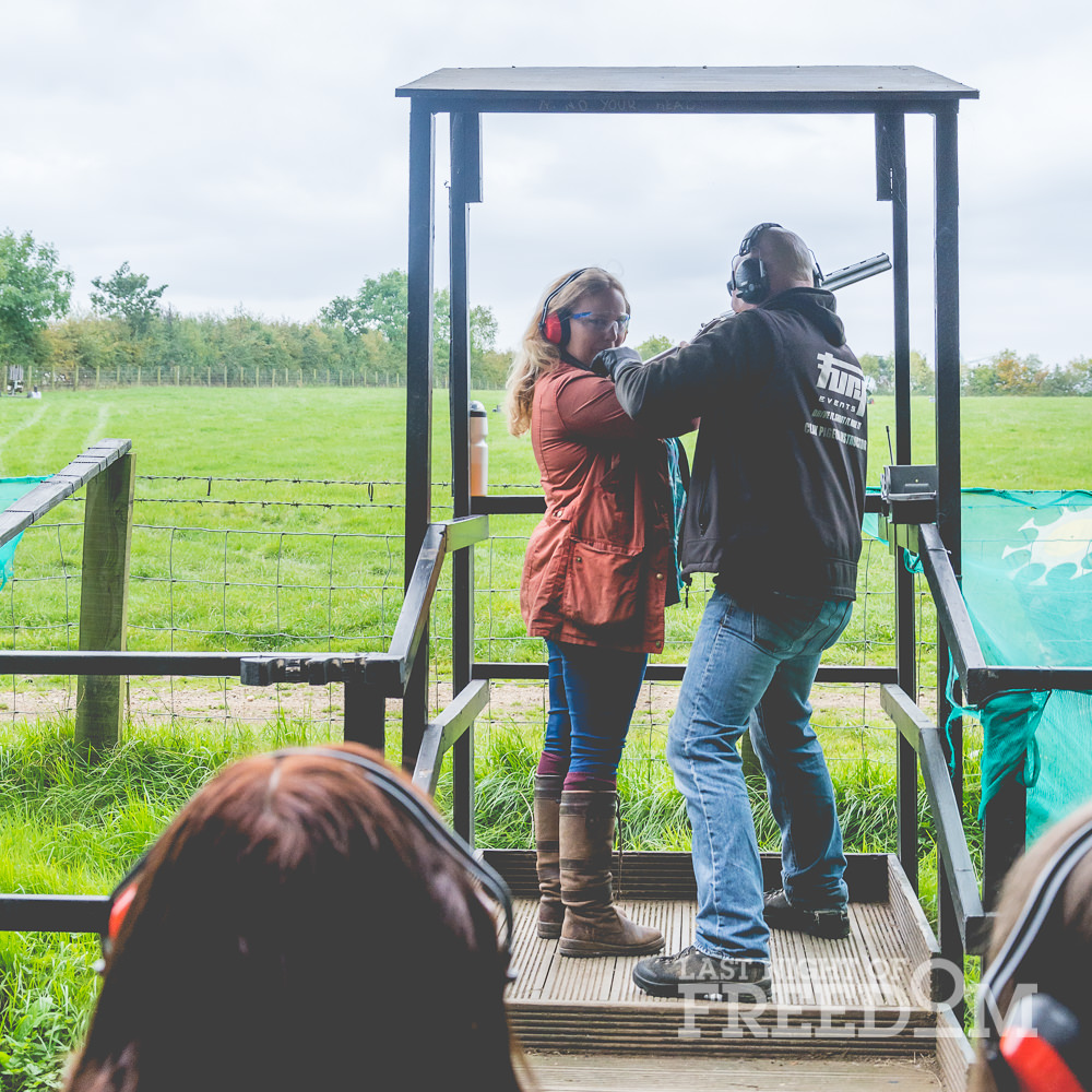 A girl turning to face the camera whilst being shown how to fire a gun