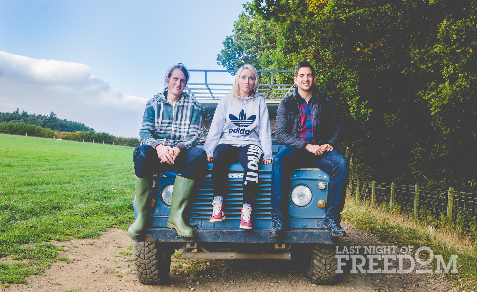 Two boys and a girl sitting on the front of a Jeep
