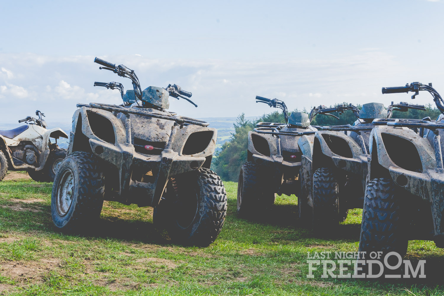 Some quad bikes lined up on a grassy hill