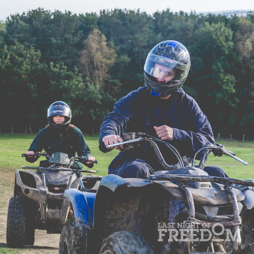 A girl and a boy riding quad bikes