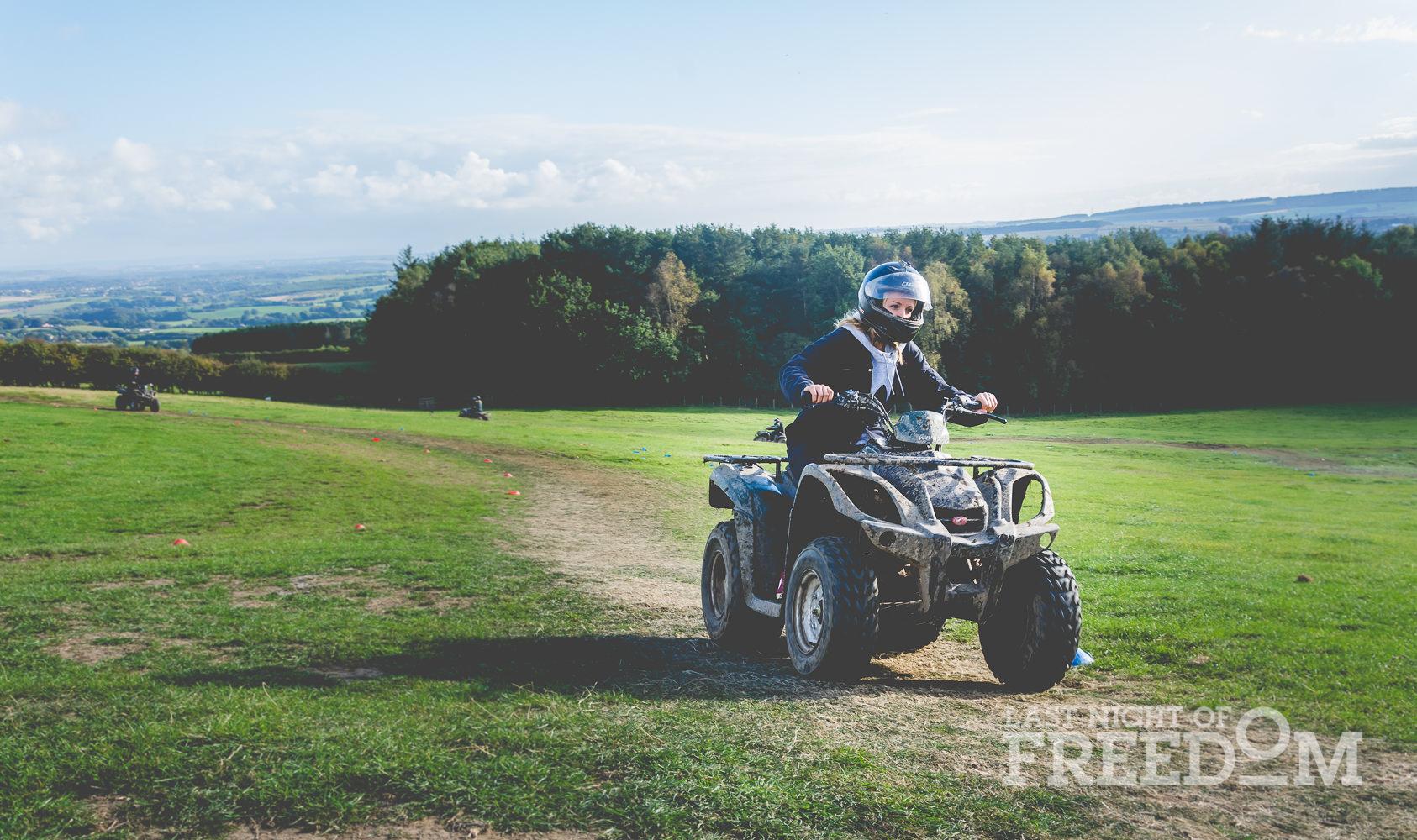 A girl riding a quad bike around the track