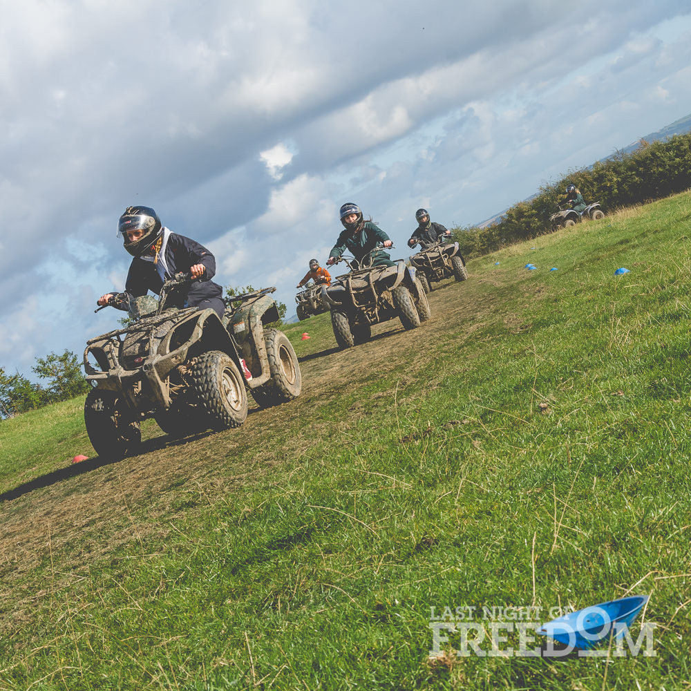 Five people racing quad bikes around a field