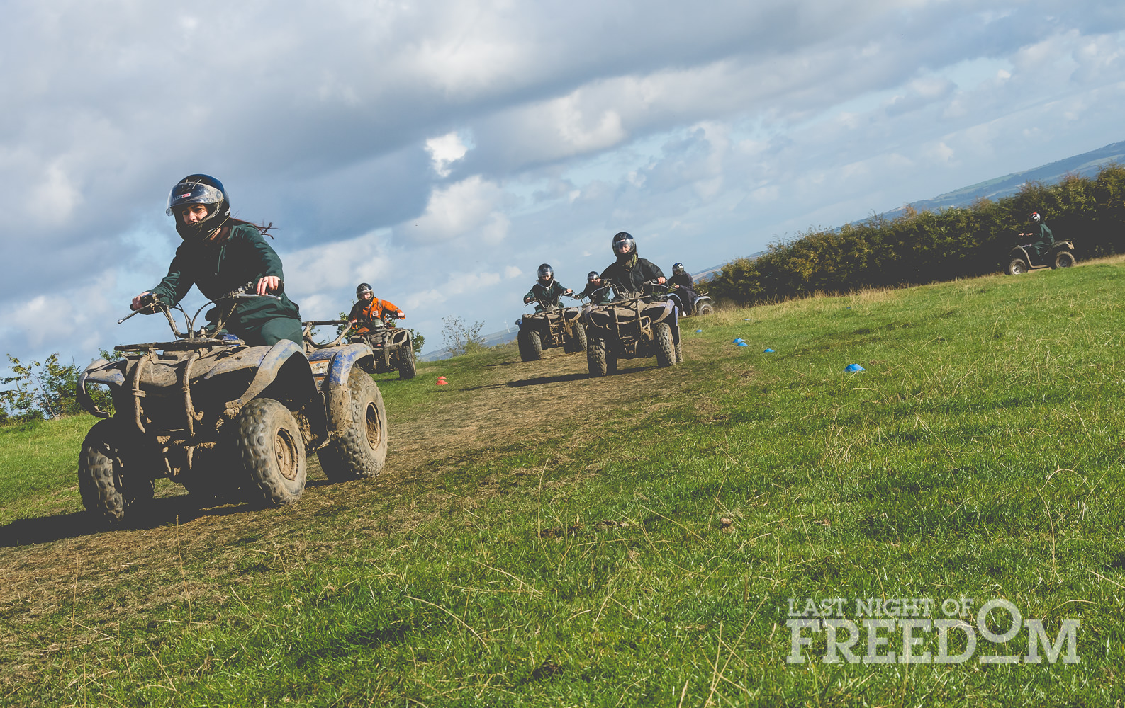 Seven people racing on quad bikes