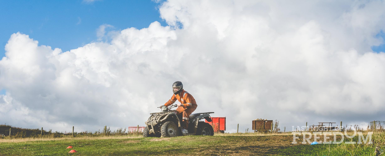 A man wearing orange overalls, riding a quad bike