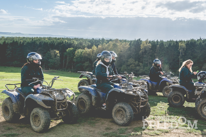 LNOF staff sitting on quad bikes, listening to instructions