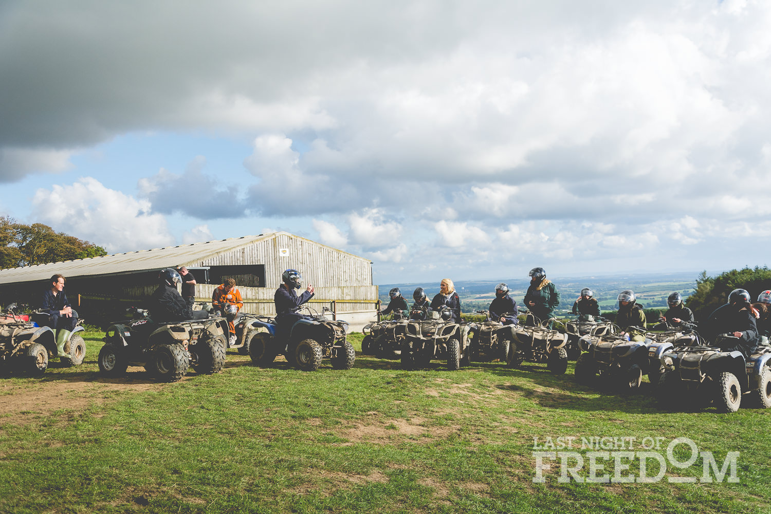 Lots of people sitting on quad bikes in a field, with a cloudy sky above them