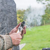 A man holding a gun with it smoking after being shot