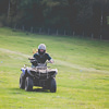 A girl riding a quad bike away from the woods
