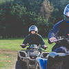 A girl and a boy riding quad bikes