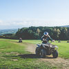 A girl riding a quad bike around a grassy track