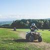 A girl riding a quad bike around a grassy track