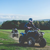 People riding quad bikes on a grassy hill