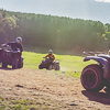 Sun rays shining through the cloud, with people on quad bikes in the foreground