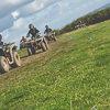 Five people racing quad bikes around a field