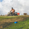 A man wearing orange overalls, riding a quad bike
