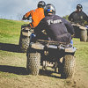 A photo of people driving quad bikes, taken from behind