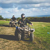 A front shot of people driving quad bikes