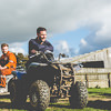 Two men sitting on quad bikes with a barn in the background
