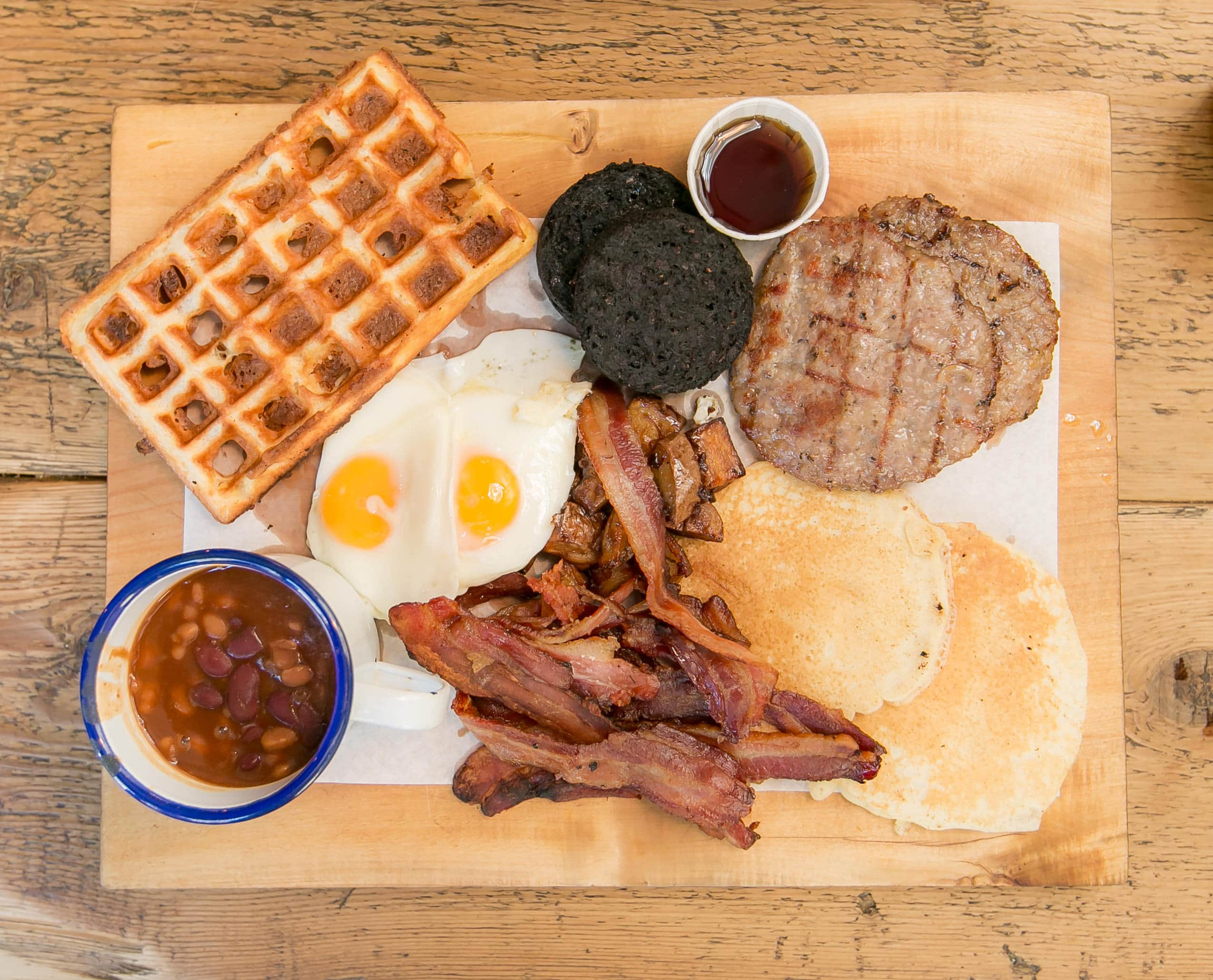 The All In breakfast at Longhorns, including: bacon, eggs, potatos, pancakes, sausages, beans, black pudding, waffle and maple syrup