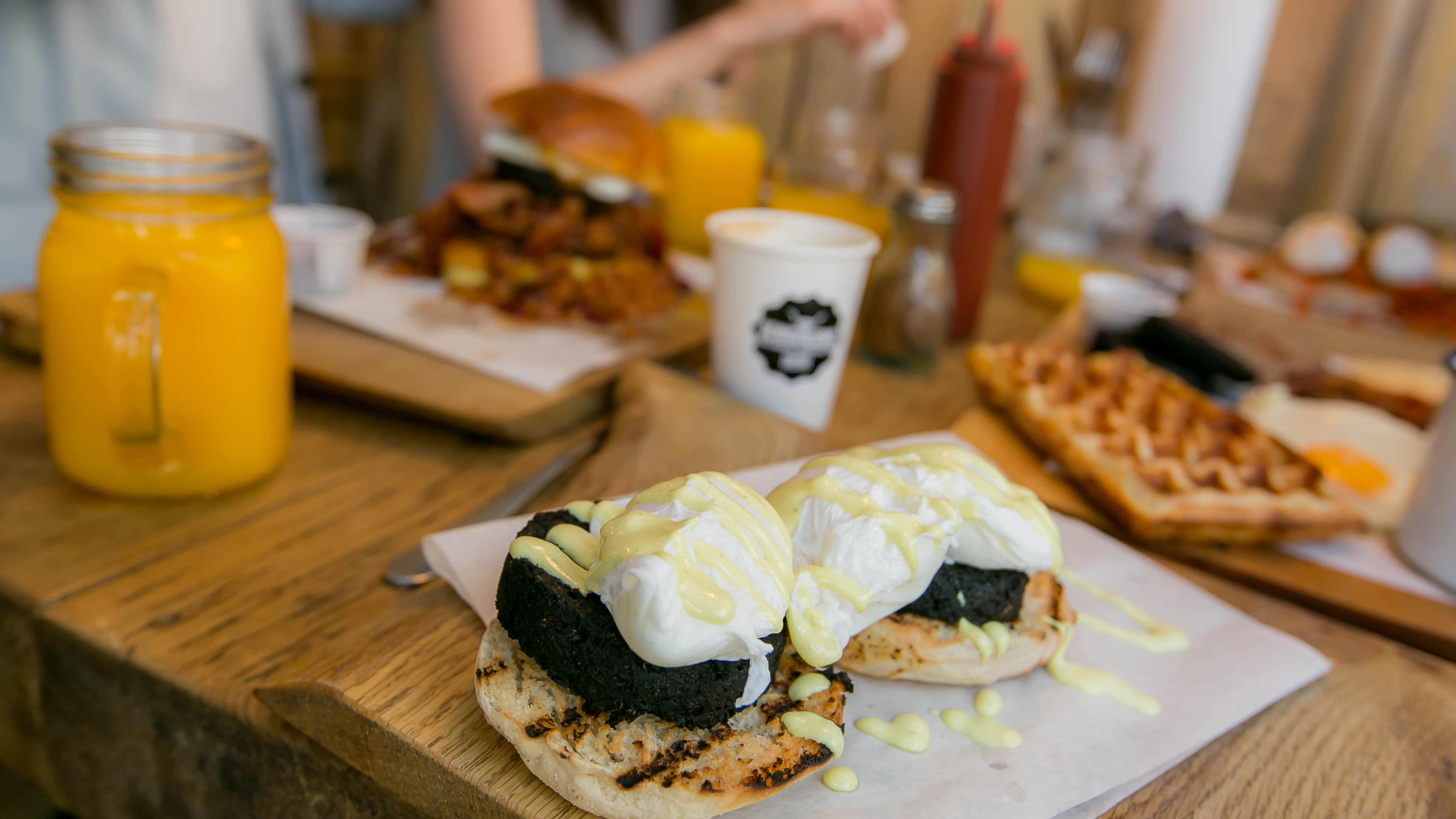 Black Pudding Benedict on table in front of other breakfasts and drinks
