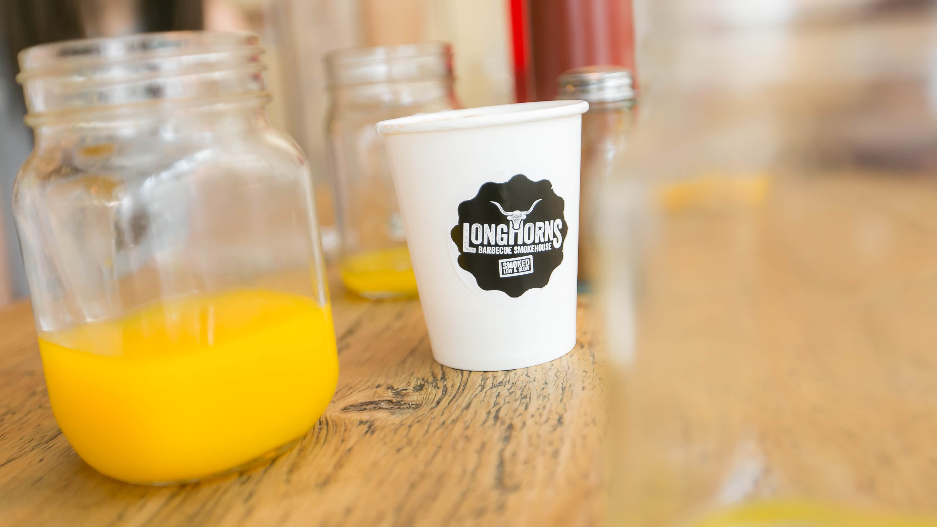 Orange juice in a glass jar alongside a Longhorns branded coffee cup