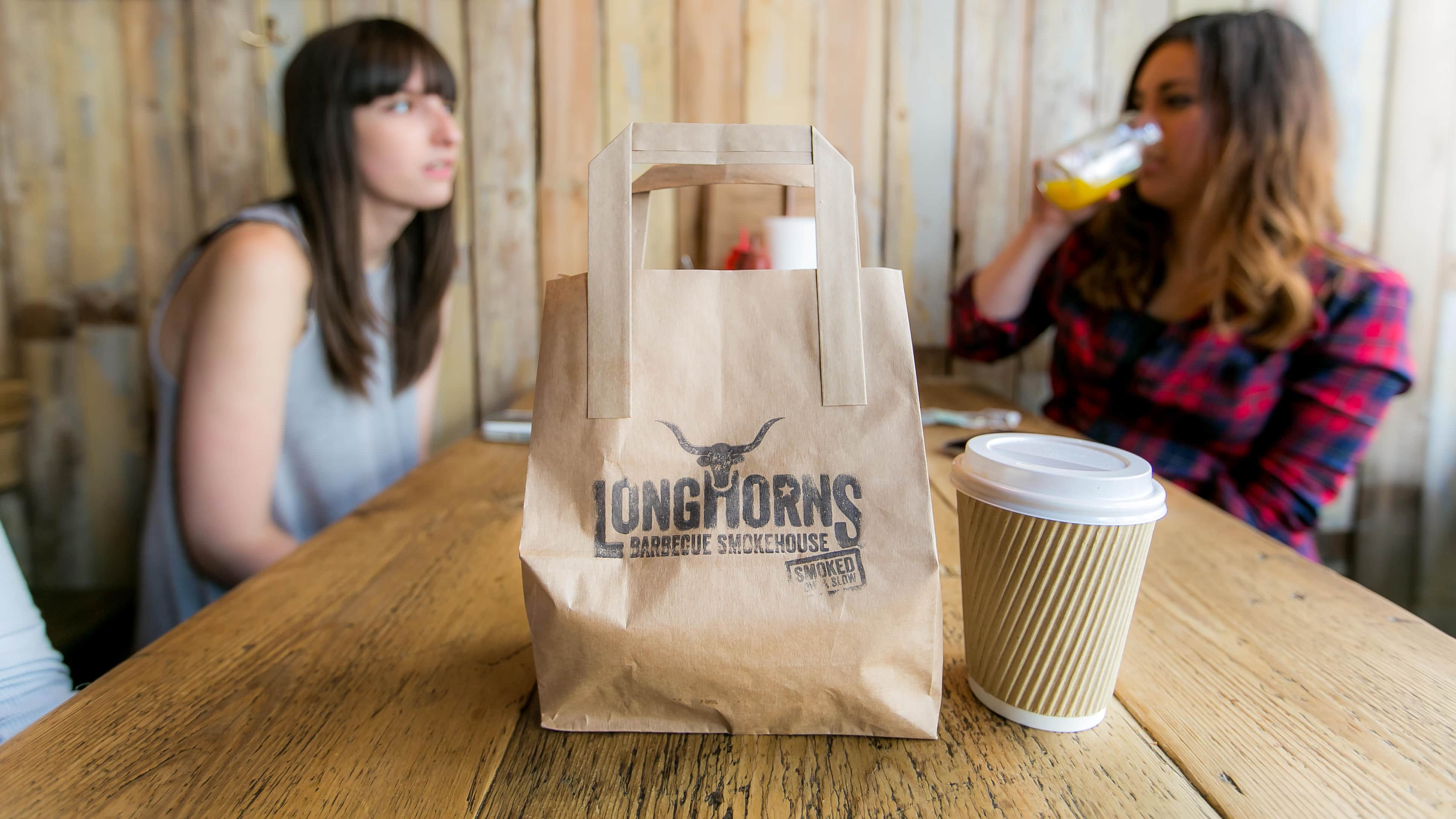 Longhorns branded takeaway bag and coffee cup, with two LNOF staff sat in the background