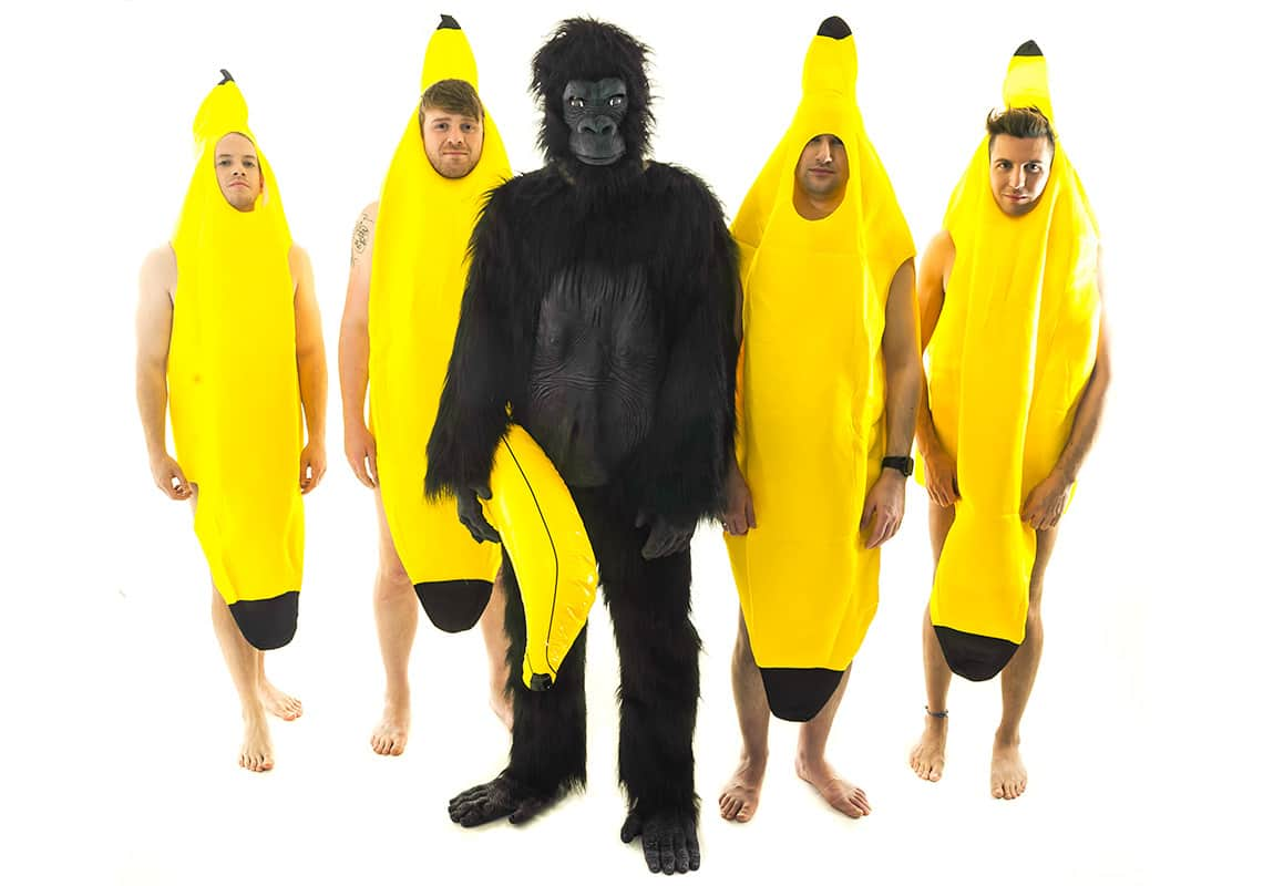 a gorilla and four men dresses as bananas