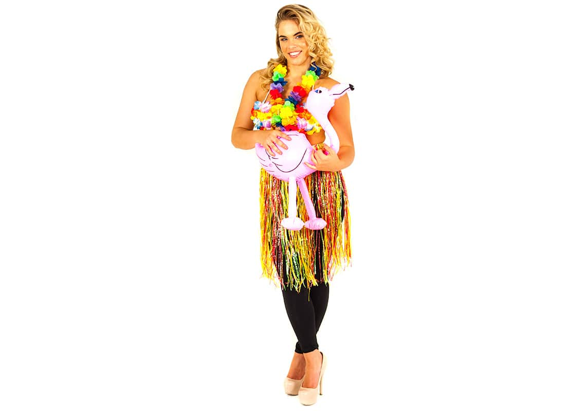 sexy hula girl in grass skirt holding an inflatable pink flamingo