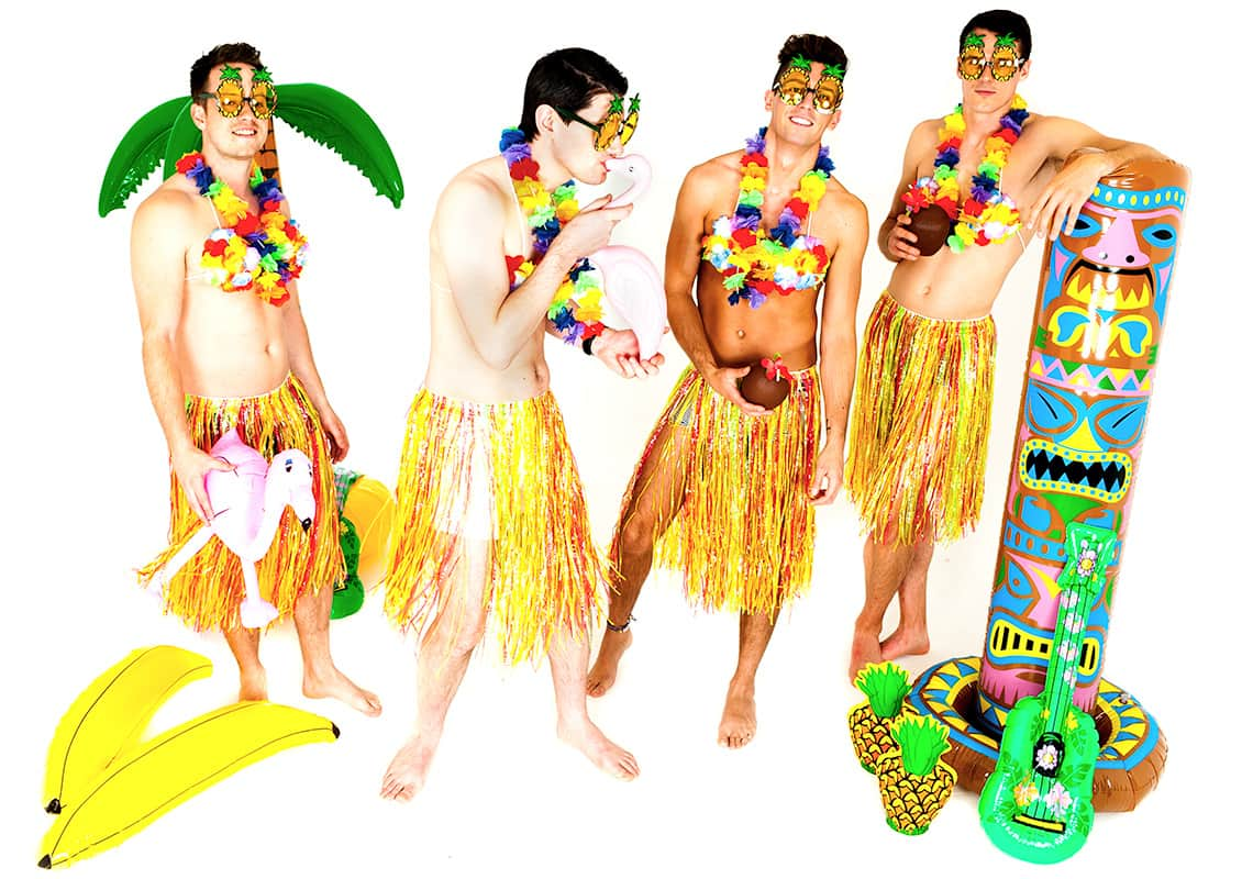 four Hawaiian hula boys wearing grass skirts in an inflatable paradise