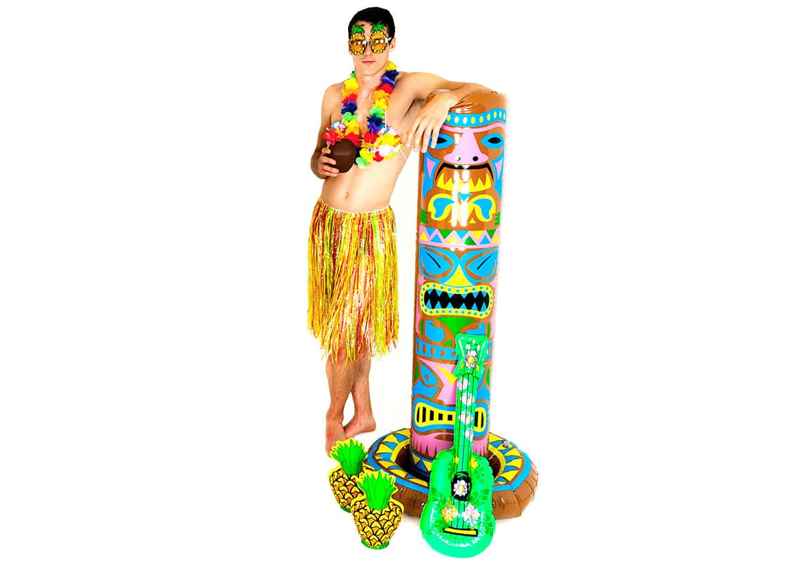 man dressed as a hula girl casually leaning against a Tiki pole
