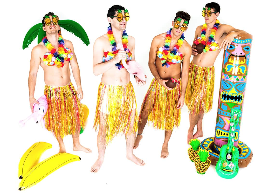 four pretty hula men in grass skirts with inflatable palm trees