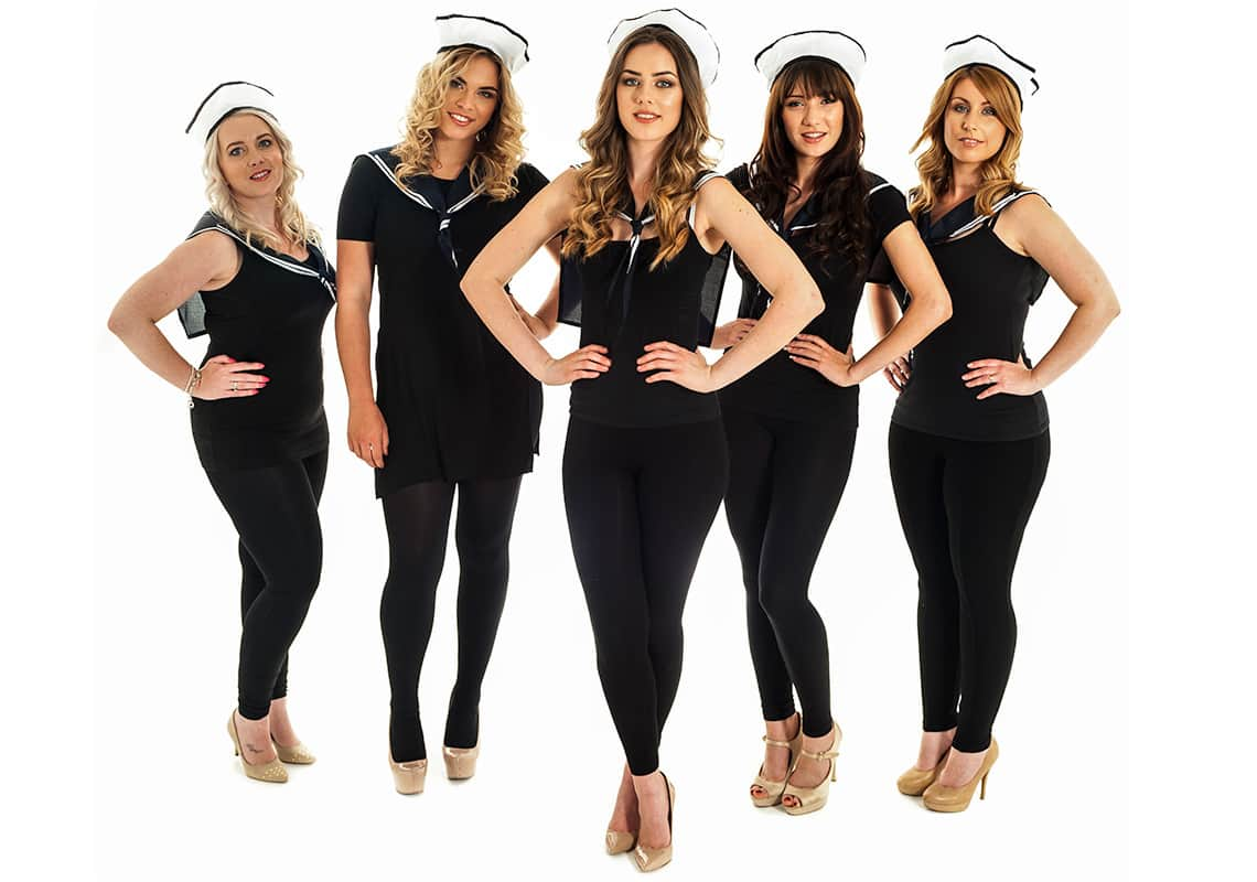 five women in black outfits and sailor hats