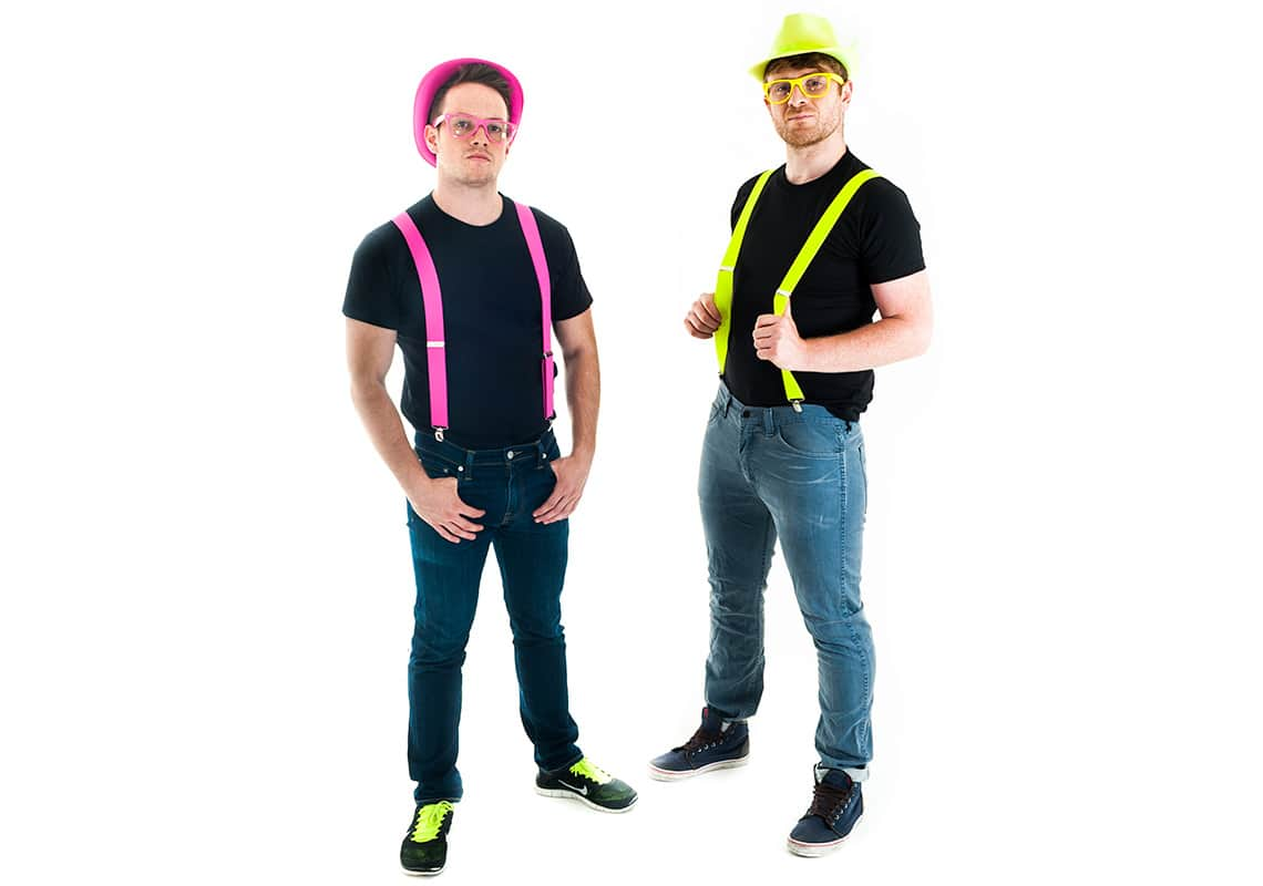 Two men in neon pink and yellow braces, glasses and hats