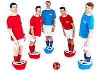 five men dressed in Subbuteo costumes tilting like players