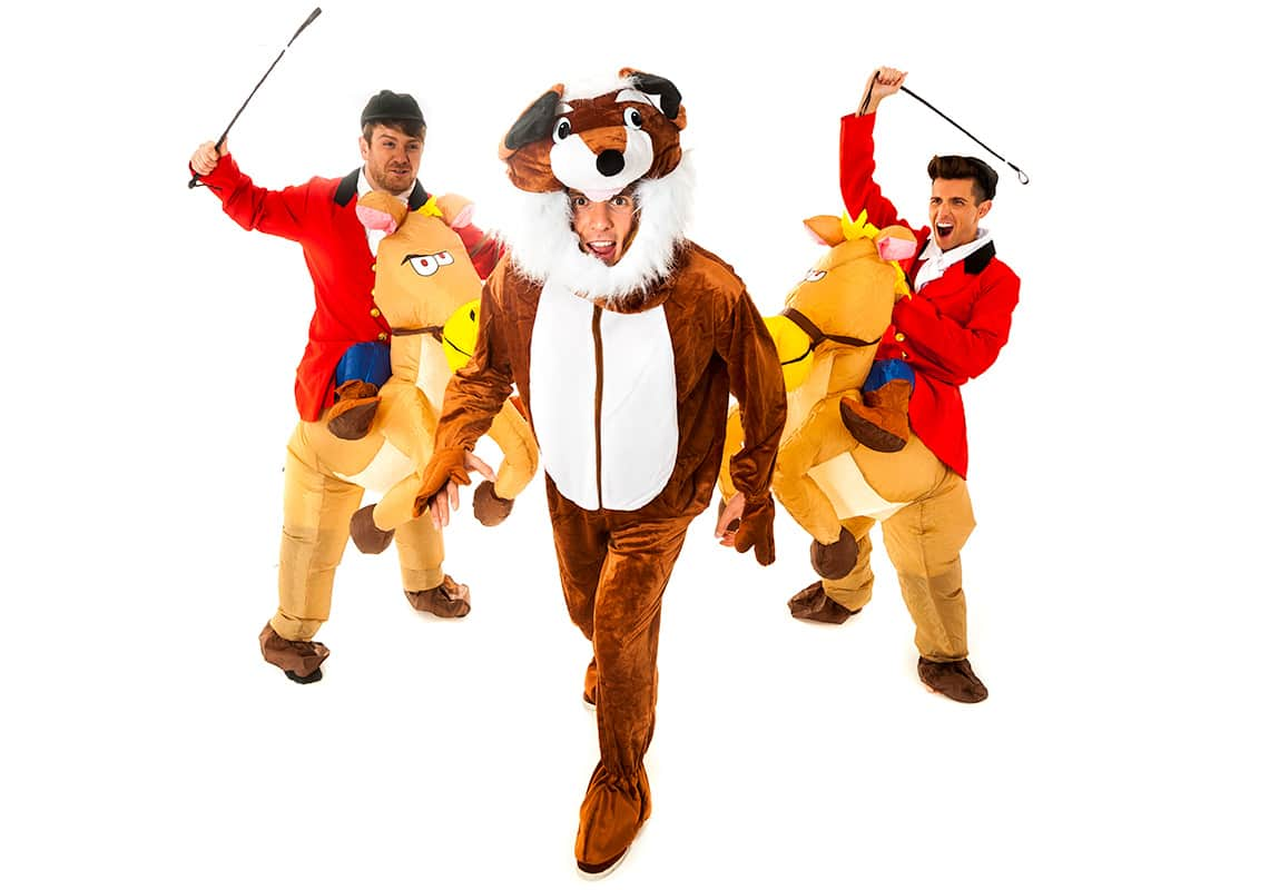 two men dressed as hunters on inflatable horseback chasing a man in a fox costume
