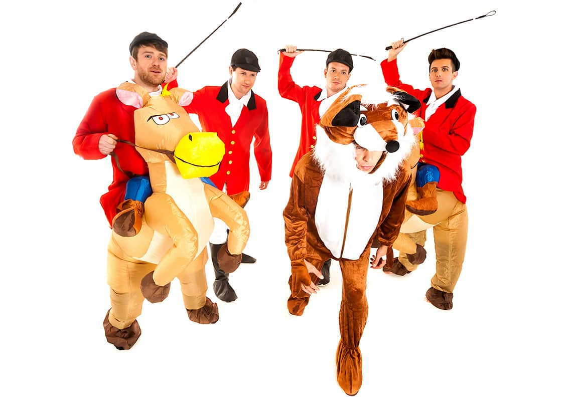 a group of men dressed as hunters chasing a man dressed as a giant ginger fox