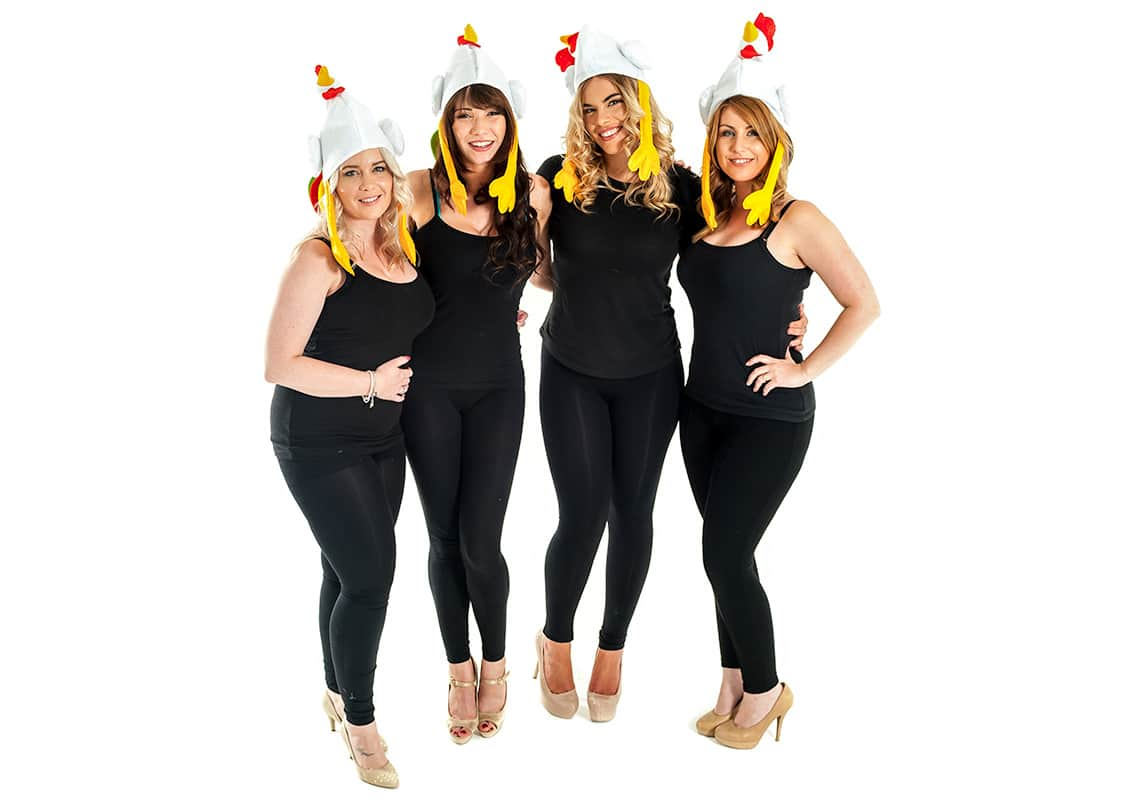 a hen party wearing chicken hats with their arms around each other