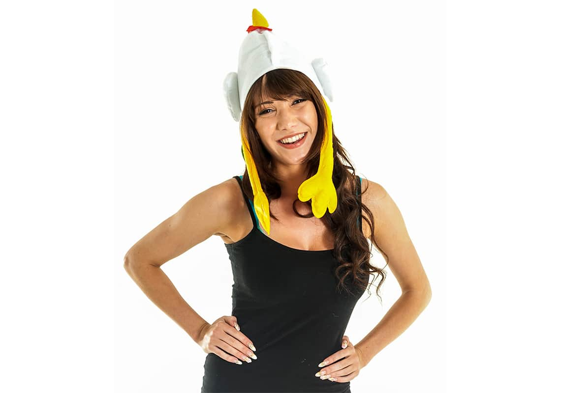 a close-up shot of a brunette woman wearing a chicken hat and laughing