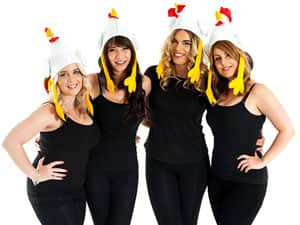 A hen group in black outfits wearing chicken hats