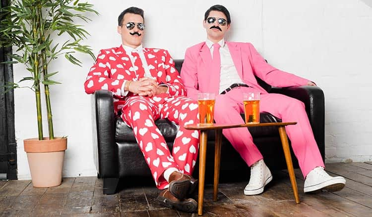 Two men sat on a leather sofa in Opposuits and wearing comedy moustaches, with beer on a table in the foreground
