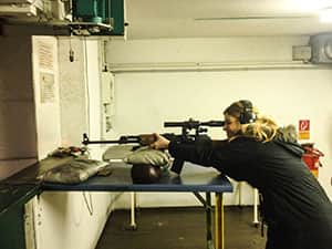 Cheryl firing a rifle