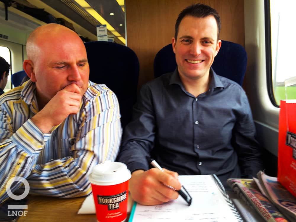 Two men sat on a train and drinking tea
