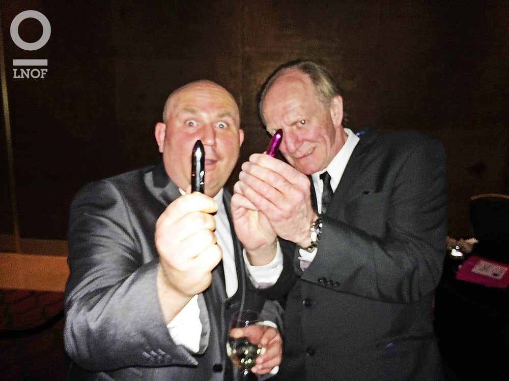 Two men in suits, holding up bullets to the camera