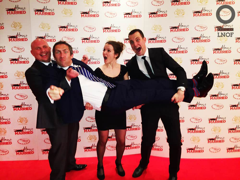 Two men and a woman, carrying another man at the Almost Married film premier