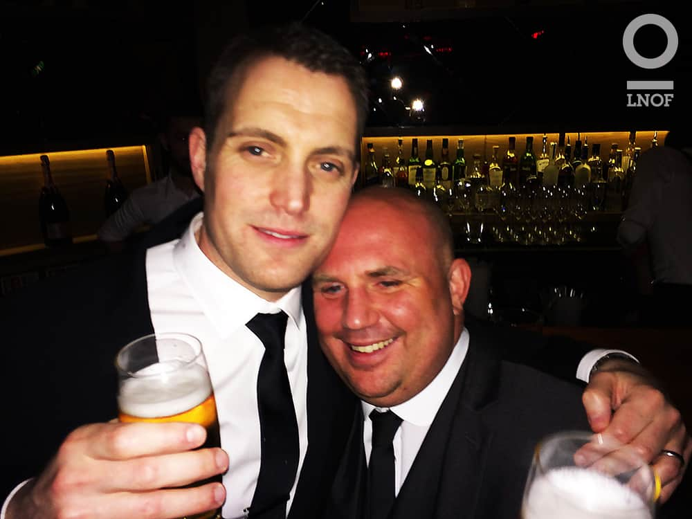 Two men in suits, hugging whilst holding pints of beer