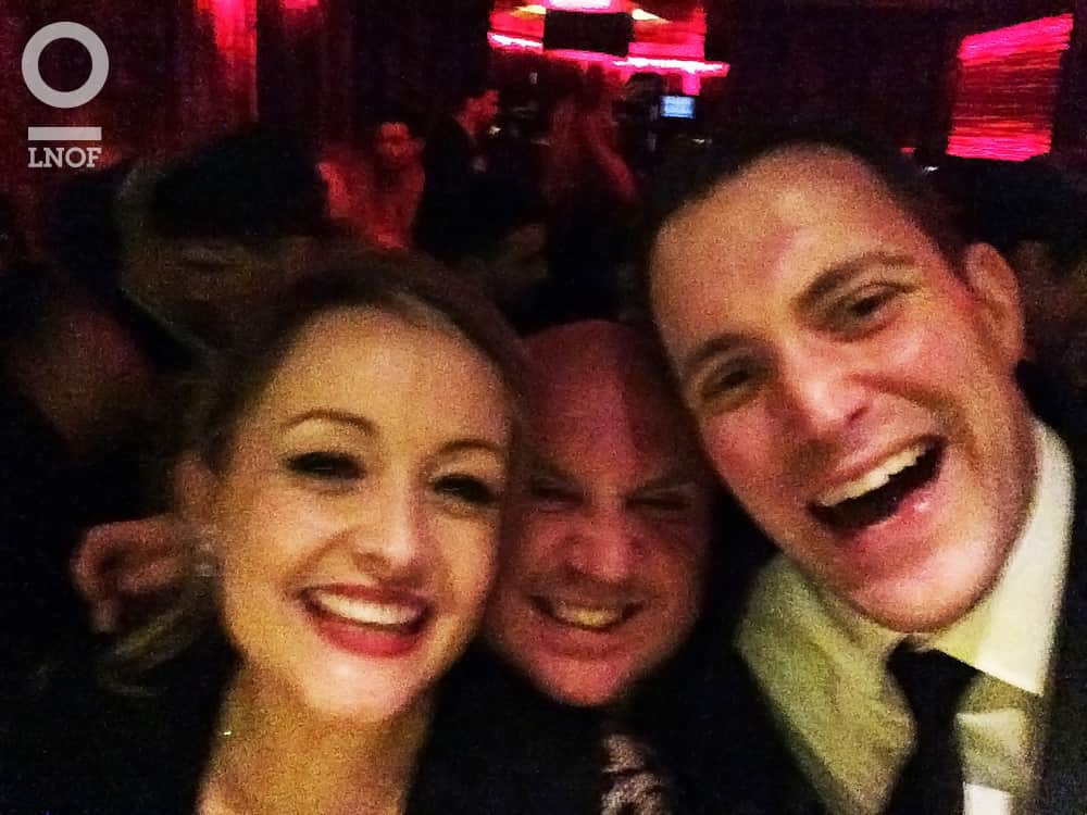 A selfie of two men laughing and smiling whilst posing with a woman