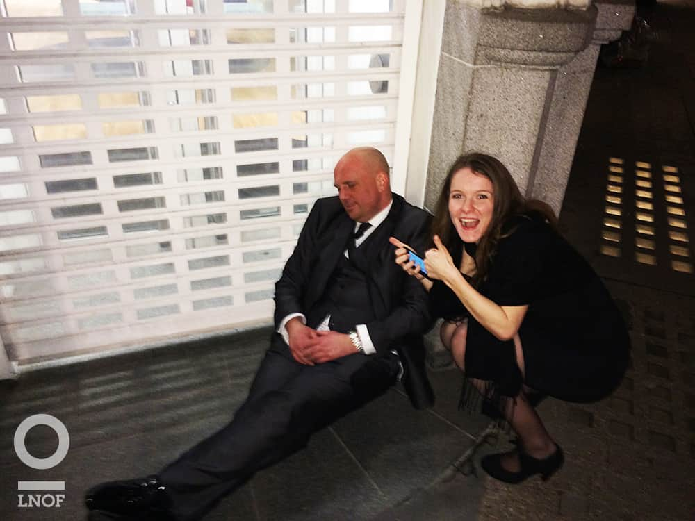 A man in a suit, asleep in a doorway whilst a smartly dressed woman holds her thumbs up and poses next to him
